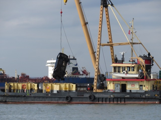 Floating derrick lifts SUV from water